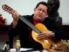 Chávez, una vida dedicada a la lucha por el pueblo. Chávez toca la guitarra durante un Consejo de Ministros en el palacio presidencial de Miraflores en Caracas.