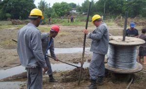 Los trabajadores recuperan las líneas eléctricas afectadas en el poblado de Caracusey. (foto: Carmen Rodríguez Pentón)