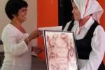 Anilia Moreno entrega el reconocimiento a Felicia Estepa Valdivia, Directora e Instructora de la agrupación. (foto: AIN)