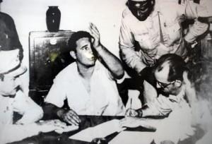 Fidel, en el vivac santiaguero, hace declaraciones mientras Sarría, inclinado hacia delante, sigue atentamente sus palabras. Chaviano escucha torvo.