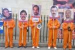 Los activistas se presentaron vestidos con uniformes de color naranja similares a los de presos de cárceles estadounidenses y pancartas con las fotos de los Cinco.