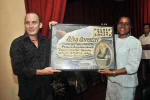 """Pedro de Jesús recibió el premio de ensayo """"Alejo Carpentier"""" de manos de Zuleica Romay, presidenta del Instituto Cubano del Libro."""