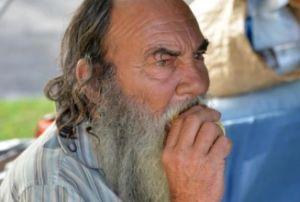 Un mendigo come un pedazo de pan en las calles de Miami.