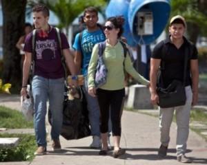 """En esta foto del 11 de julio de 2014, estudiantes cubanos salen de la Universidad Central Marta Abreu, en Santa Clara. La USIAD, tratando de convertir a jóvenes cubanos en """"agentes de cambio"""", envió su proyecto a Santa Clara e hizo conexión con un grupo cultural que se hacía llamar """"Revolución"""". Foto: Franklin Reyes/ AP"""