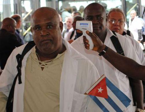 Médicos cubanas pasan el control sanitario a su llegada a Monrovia. / REUTERS