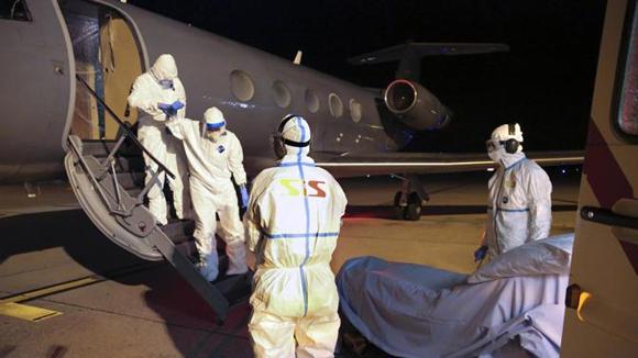 Báez pudo bajar a pie del avión que le trasladó desde África, vestido con un traje de protección y de una máscara. Foto: AFP