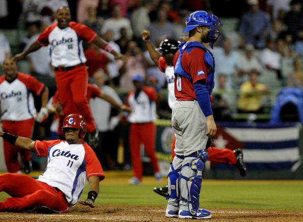 Yosvani  Alarcón(I), anota la carrera de la victoria para los Vegueros de Pinar del Río, de Cuba, frente a los Cangrejeros de Santurce, de Puerto Rico. Foto AIN.