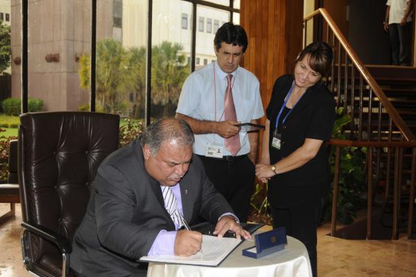 Baron Waqa firma el libro de visitantes durante su visita al Centro de Ingenieria Genética y Biotecnología. (Foto AIN)