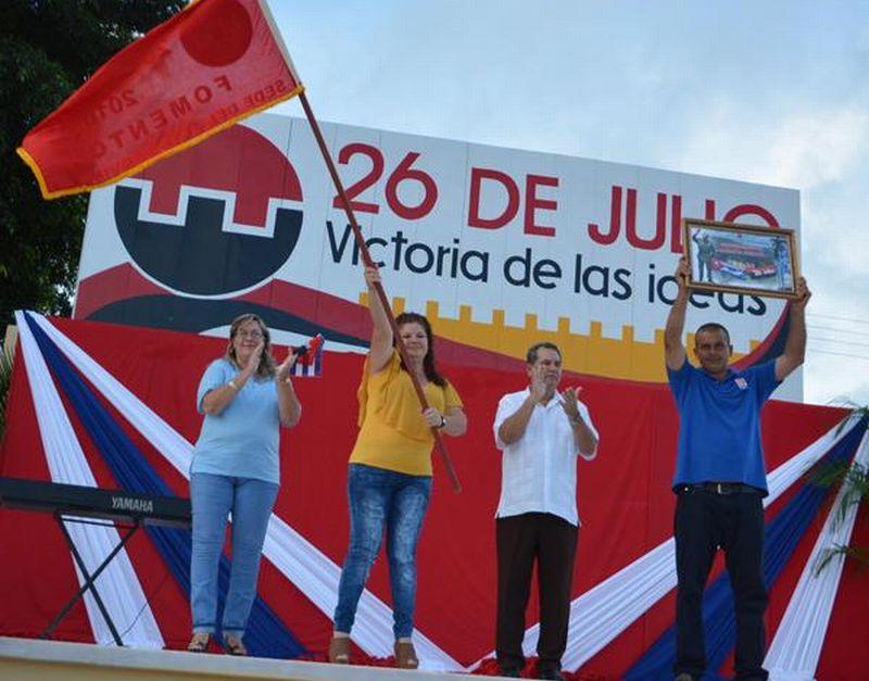 La secretaria del Partido en Fomento exhibe la bandera de municipio ganador del acto provincial por el 26 de julio. (Foto: Oscar Alfonso/ ACN)
