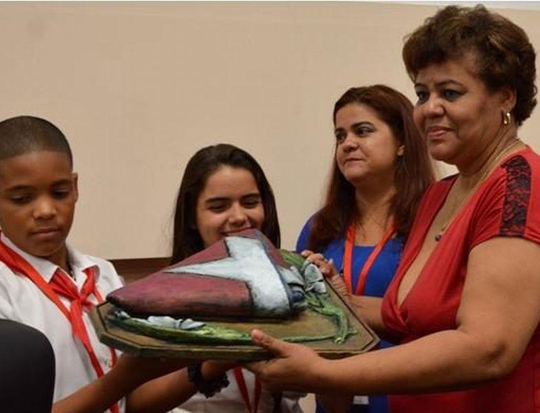 Olga Lidia Tapia recibe de manos de los pioneros un reconocimiento para Raúl Castro, una bandera cubana. (Foto: ACN)