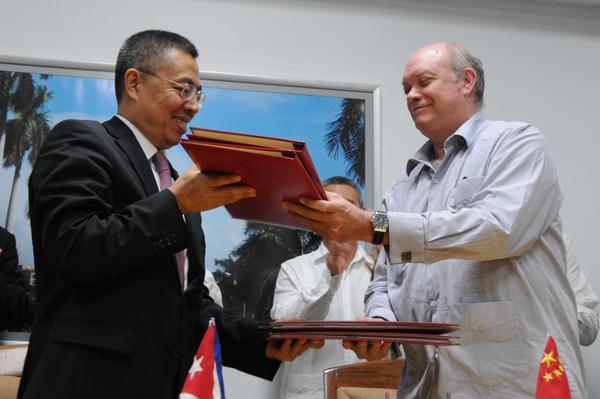 Rodrigo Malmierca y Zhang Xiangchen intercambian los documentos firmados. (Foto: ACN)