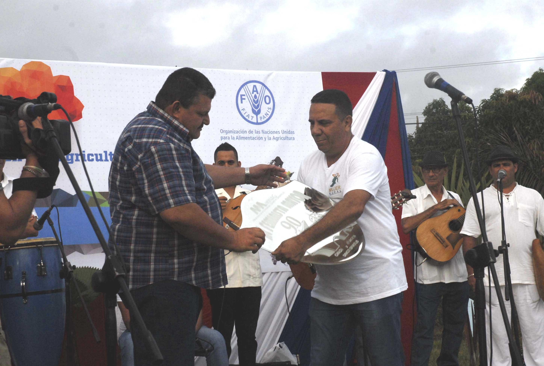 El artista Enrique Neira entrega al presidente de la ANAP una obra de arte en nombre de la Asociación de Comunicadores Sociales. (Foto: Elizabeth Borrego/ Escambray)
