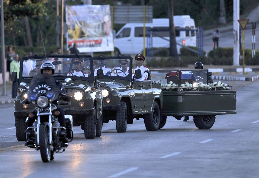 The urn with the ashes of Cuban leader Fidel Castro leaves Revolution Square in Santiago, Cuba on December 4, 2016 on its way to the cemetery. The ashes of late Cuban leader Fidel Castro were taken on Sunday to be laid to rest at a cemetery in the eastern city of Santiago de Cuba. / AFP PHOTO / PEDRO PARDO